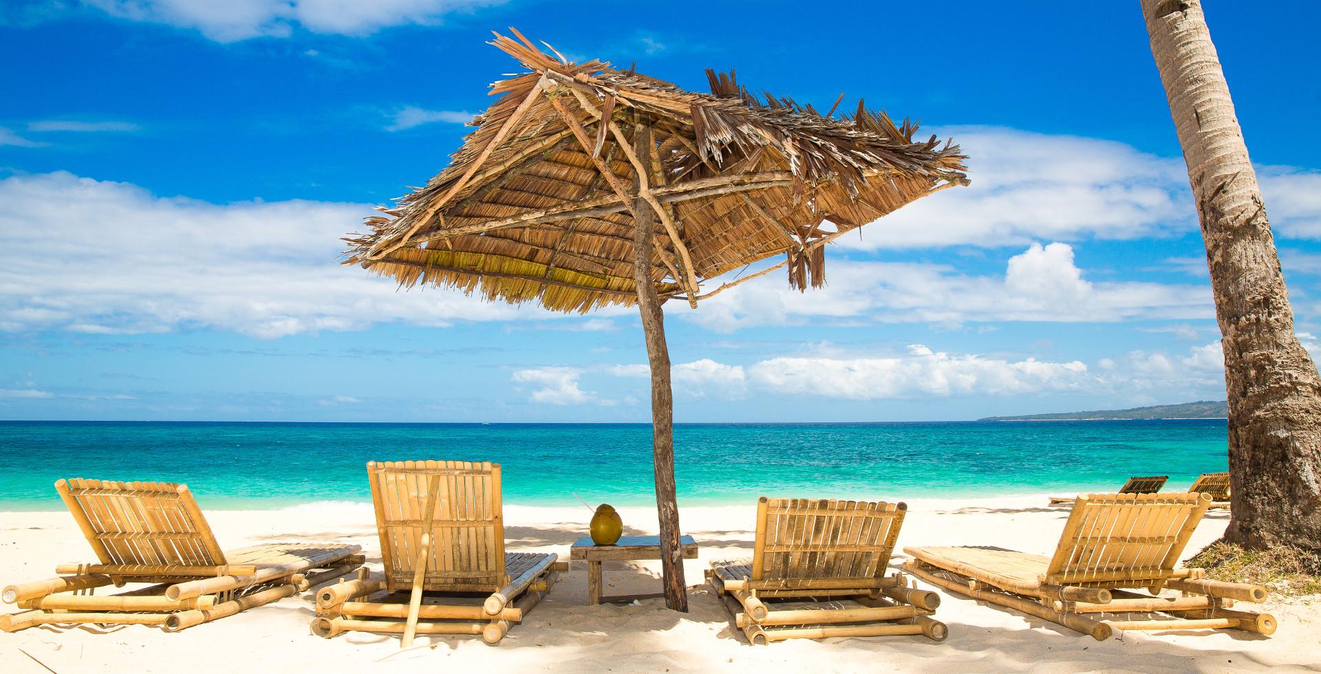 Sun umbrella and beach beds on tropical beach. Summer vacantion concept.